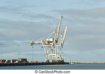 Large cranes on the wharf of a harbor