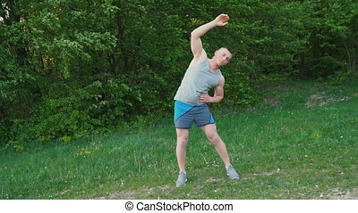 The guy warms up in the open air - Muscular guy warm-up in...