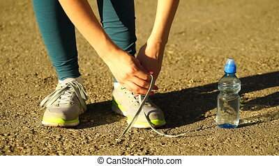 girl stopped running to tie the laces on running shoes....