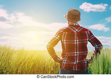 Female farmer looking at the sun on the horizon