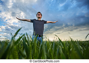 Teenager standing in a wheat field at sunset