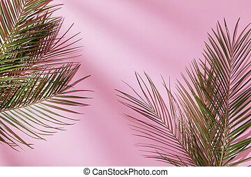 Composition with leaves in a border corner, on a pink...