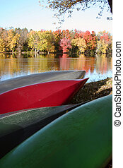Canoes on river bank with autumn fo - Colorful canoes...