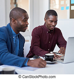 African businessmen working on a laptop in an white office