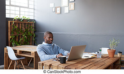 Content African businessman working on a laptop in an office...