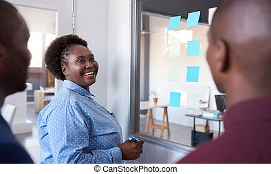 Young African businesspeople strategizing with sticky notes...