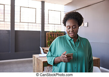 Young African businesswoman using a cellphone in an office -...