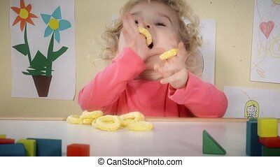 Hungry child eating corn maize crisps sitting near table in...