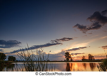Sunset over calm lake , sky reflection in water
