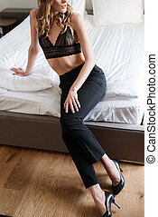 Vertical cropped view of woman sitting on bed