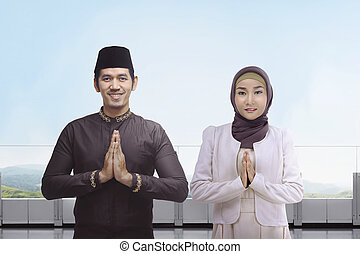 Asian muslim man and woman with traditional dress praying together