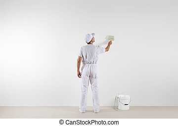 Rear view of painter man looking at blank wall, with paint brush and bucket, isolated on white room