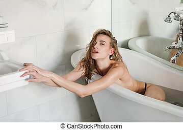Woman without clothes lying in bath with water - Young woman...