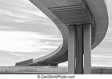 Urban concrete flyover in black and white curving to the...