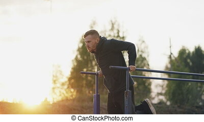 Handsome muscular young man have workout training at the park on sunset