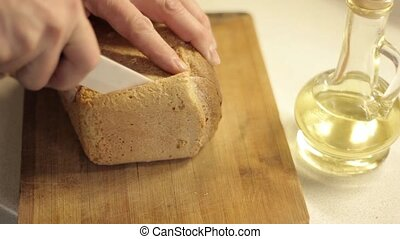 Cuts slice of bread for French toast.
