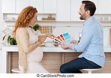Mature couple discussing shades of paint color - Home...