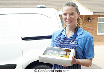 Female Baker Making Home Delivery Of Cupcakes