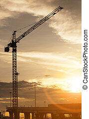 crane at construction site and sunset sky