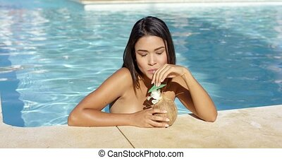Young woman drinking cocktails in the pool - Young woman...