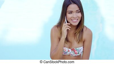 Young woman in a bikini talking on a mobile phone at the...