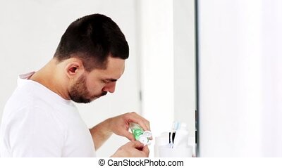 man with lotion or toner cleaning face at bathroom - beauty,...