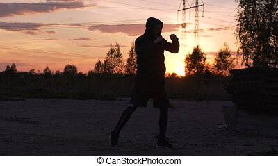 Silhouette of young man boxer training for kicking on sunset at city park