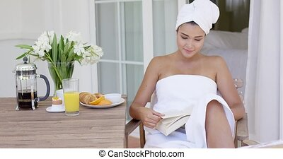 Woman in bath towel reading book at table - Cheerful young...