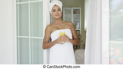 Beautiful woman wrapped in towel looking outside - Single...