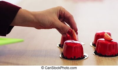 chef decorating mirror glaze cakes at pastry shop - cooking,...