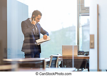 Businessman talking on a mobile phone while looking at...