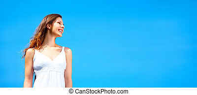 Beautiful young woman - Beautiful young woman under blue sky...