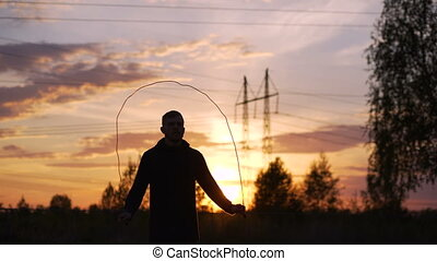 Silhouette of young man kick boxer training with skipping rope on sunset at city park