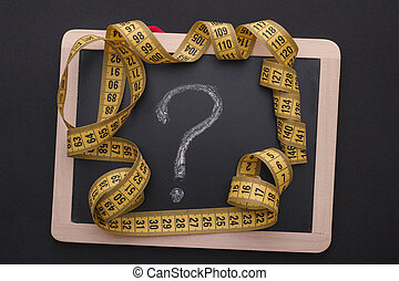 Measuring tape on blackboard with question mark