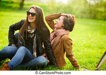 Two pretty young women cheerfully spend time in the spring...