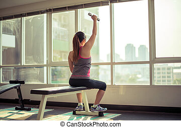 Woman exercising with dumbbells - Young asian woman...