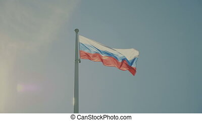 Russian flag on the flagpole waving in the wind against a...