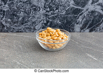 Roasted salted peanuts - Glass bowl of nuts in closeup on a...