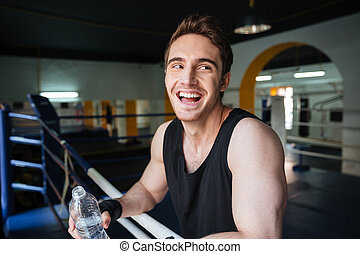 Side view of laughing boxer relaxing in boxing ring and...