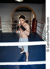 Man boxer wearing boxing gloves looking camera ans posing on...