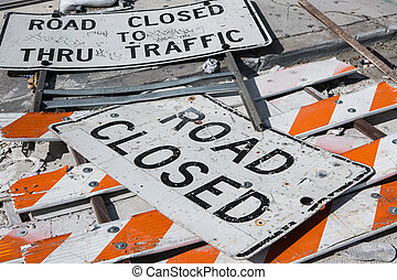 Road Closed Signs fell down on a road with broken barricades...