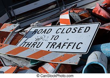 A dump of Road Closed Sign fell down on a road with broken...