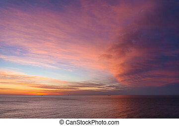 Beautiful sunrise, sunset sky over calm ocean