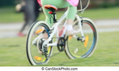 Happy little girl riding a bicycle on the meadow in summer...