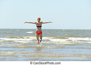 Slim young woman running into sea waves with outstretched...
