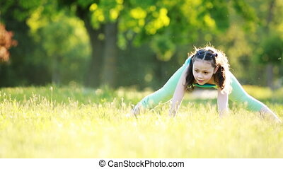 Cheerful and happy little girl dancing and playing on green grass in the park.