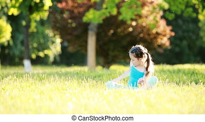 Cute little girl sitting in the meadow and playing in the park in summer day.