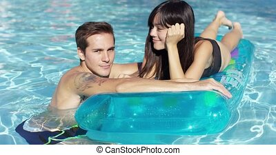 Young couple in love relaxing in the pool with the smiling...