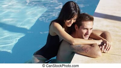 Woman in black swim suit hugs her boyfriend as he rests his...