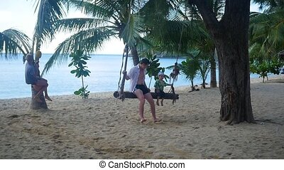 a guy and a kids swinging on a rope swing on the beach. Tropical island